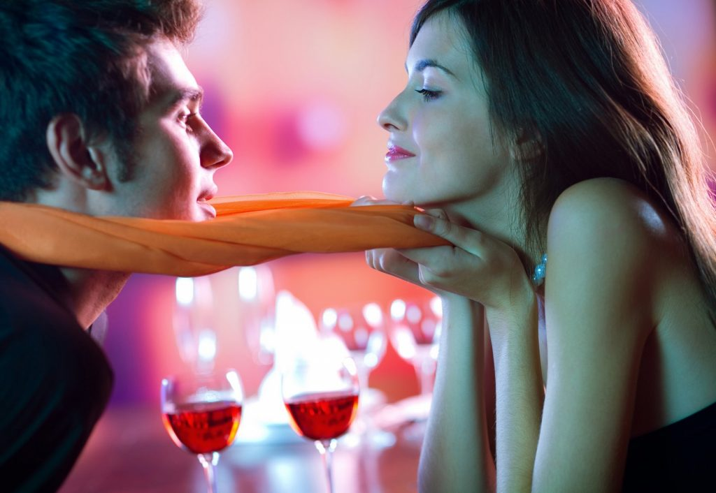 Young happy couple kissing in restaurant, celebrating